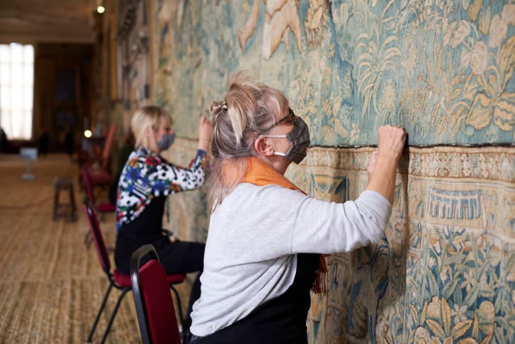 Textile conservators from the National Trust sewing the lower border onto the 400-year-old tapestry which has returned to Hardwick Hall, Derbyshire, after over two years of conservation.