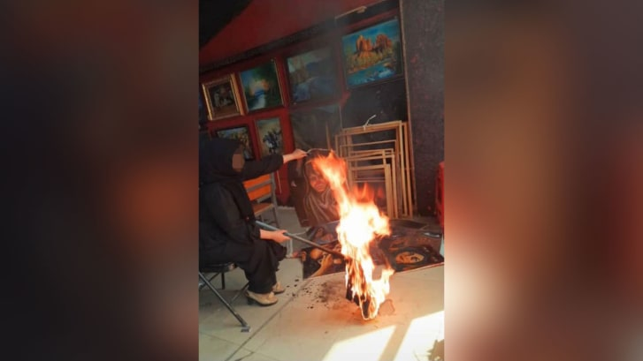 An Afghan artist burns her artwork at a studio days after the Taliban takeover of the country. Part of this image has been blurred by CNN for safety reasons.