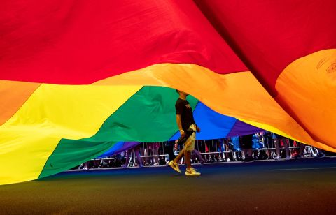 A participant walks under a large rainbow flag. Craig Ruttle/AP