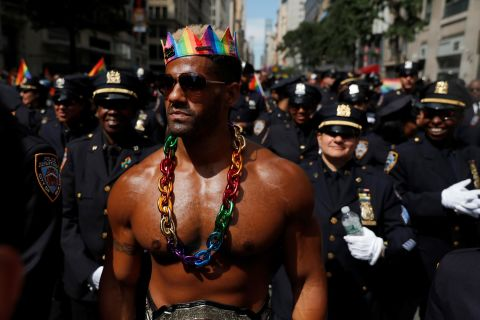 A man walks with New York City Police officers as they take part in the parade. Jeenah Moon/Reuters