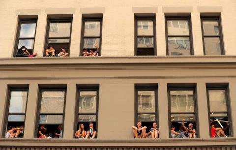 People watch from windows on 6th Avenue along the parade route. Lucas Jackson/Reuters