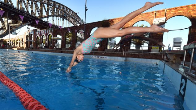 Swimmers dive into the North Sydney Olympic Pool.