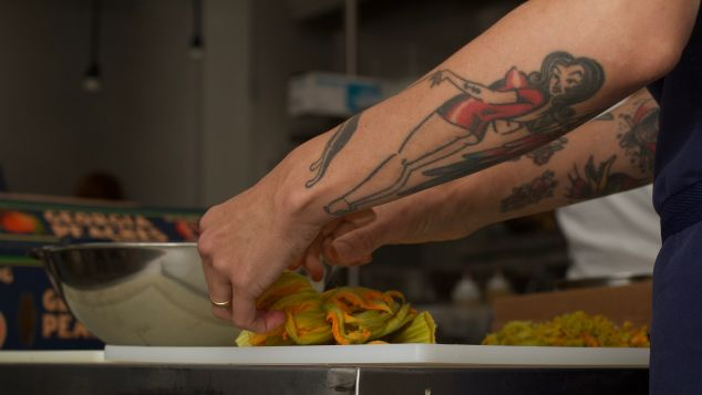 Chef Whitney Otawka prepares squash blossoms for a dish.