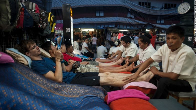 Tourists get a foot massage in Khao San road in Bangkok, Thailand.